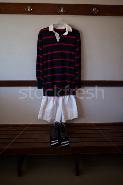Shoes and socks on wooden bench against rugby uniform Stock photo © wavebreak_media