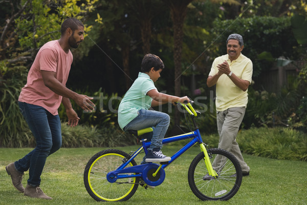 Father and grandfather motivating boy while riding bicycle Stock photo © wavebreak_media