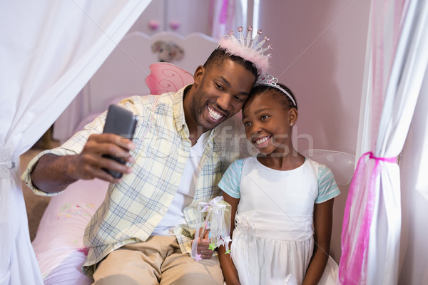 Father and daughter taking selfie while sitting on bed at home Stock photo © wavebreak_media