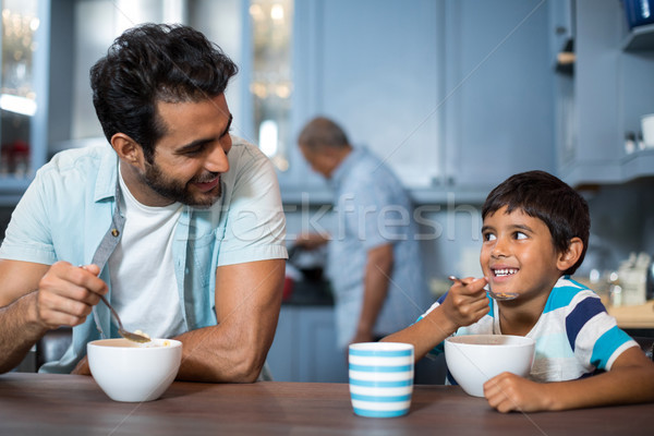 Father and son having breakfast with man in background Stock photo © wavebreak_media