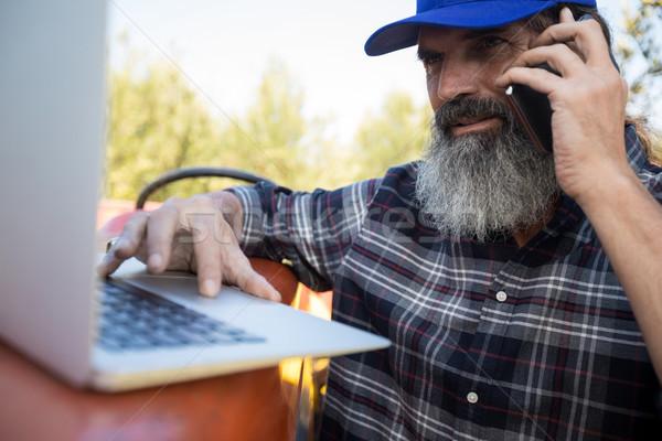 Man using laptop while talking on mobile phone Stock photo © wavebreak_media