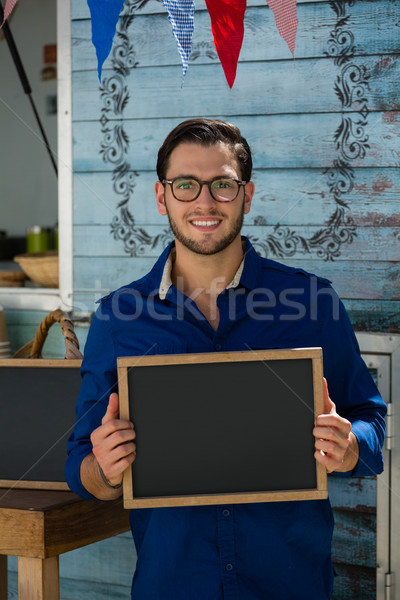 Smiling owner holding writing slate while standing by cafe Stock photo © wavebreak_media