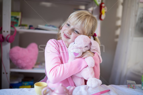 Smiling girl playing with a teddy bear and toy kitchen set Stock photo © wavebreak_media