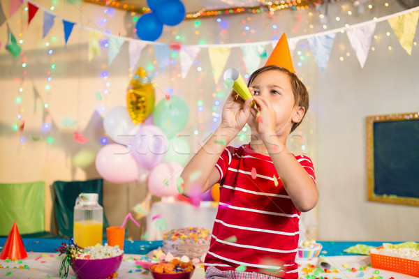 Cute boy blowing party horn during birthday party Stock photo © wavebreak_media