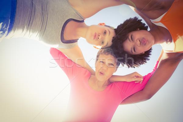 Sporty women with arms around posing down to camera  Stock photo © wavebreak_media