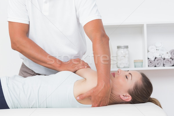 Doctor stretching a young woman back  Stock photo © wavebreak_media