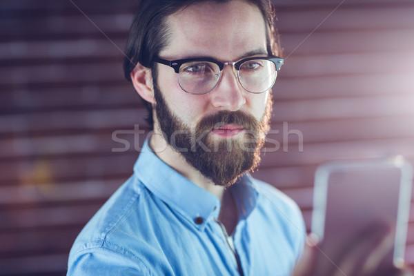 Hipszter néz mobiltelefon téglafal telefon férfi Stock fotó © wavebreak_media