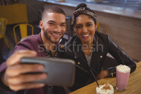 Smiling man with friend taking selfie in cafe Stock photo © wavebreak_media