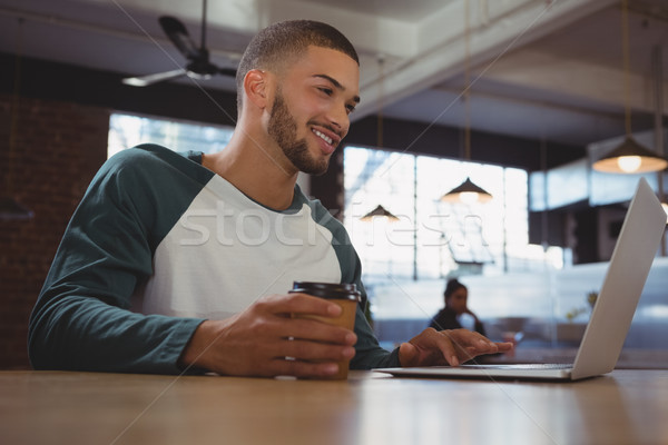 Man with coffee cup using laptop in cafe Stock photo © wavebreak_media