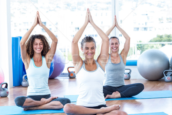 Women doing lotus pose with hands joined overhead Stock photo © wavebreak_media