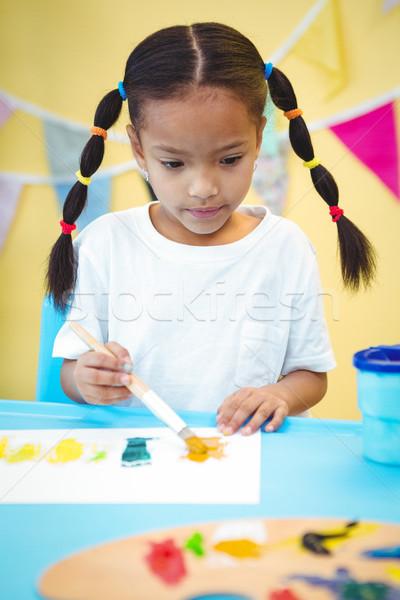 Focused girl using a paintbrush Stock photo © wavebreak_media