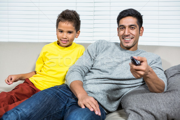 Smiling father ans son watching tv on the sofa Stock photo © wavebreak_media