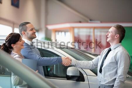 Confident salesman showing car to customer in showroom Stock photo © wavebreak_media