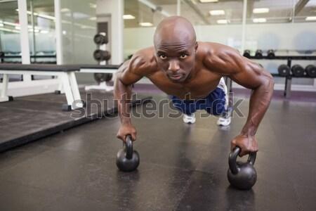 Muscular man doing push up with kettlebells Stock photo © wavebreak_media