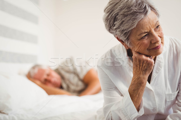 Stock photo: Worried senior woman sitting on bed