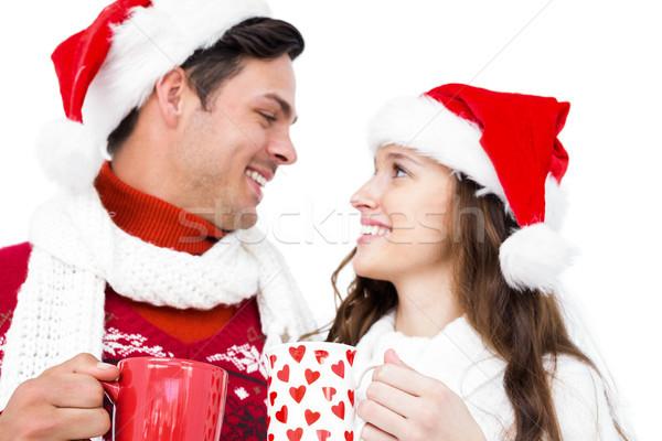 Happy couple with santa hats holding mug Stock photo © wavebreak_media