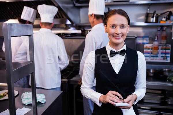 Sorridere cameriera nota commerciali cucina ritratto Foto d'archivio © wavebreak_media