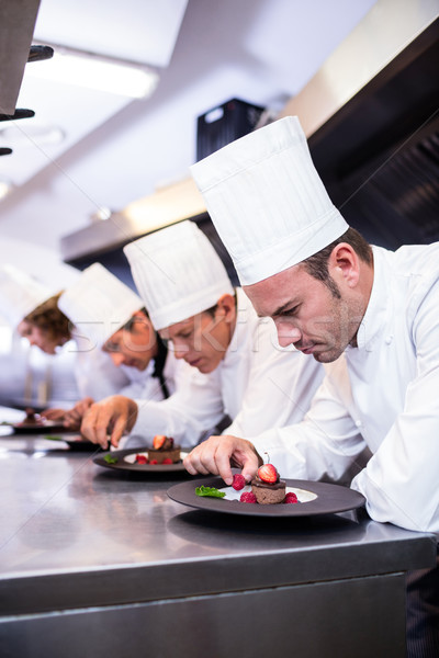 Team of chefs finishing dessert plates in the kitchen Stock photo © wavebreak_media