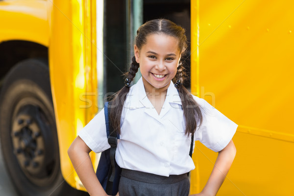Smiling schoolgirl standing in front of school bus Stock photo © wavebreak_media