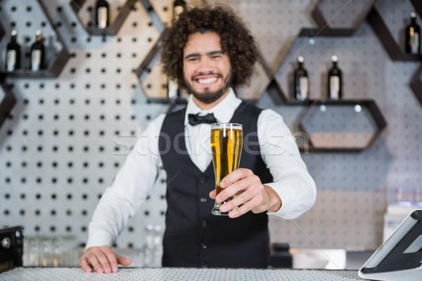 Bartender holding glass of beer in bar counter Stock photo © wavebreak_media