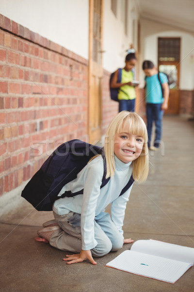 Cute pupil kneeling over notepad at corridor Stock photo © wavebreak_media