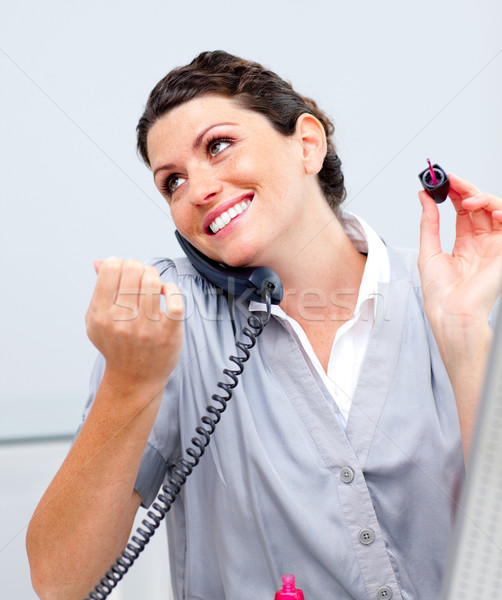 Charming woman on phone painting her nails Stock photo © wavebreak_media