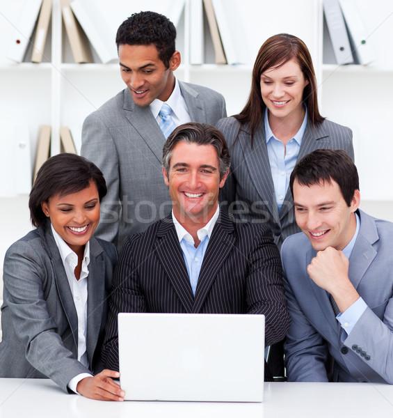 Alegre equipe de negócios olhando laptop escritório empresário Foto stock © wavebreak_media
