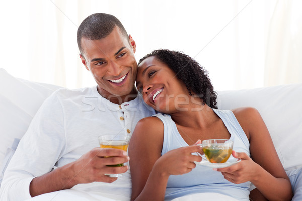 Happy couple drinking a cup of tea on their bed Stock photo © wavebreak_media
