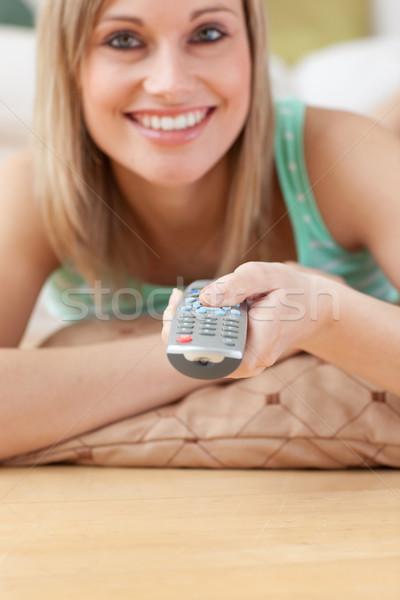 Jolly blond woman watching TV lying on the floor Stock photo © wavebreak_media