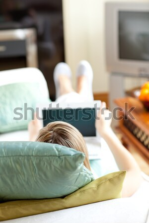 Blond woman reading a book lying on a sofa Stock photo © wavebreak_media