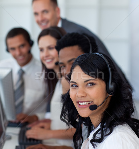 Stock photo: Portrait of a businesswoman in a call center with her multi-ethnic team