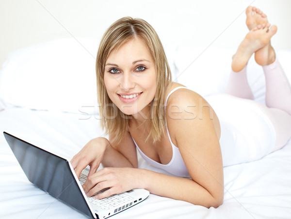 Attractive woman lying with a laptop on sofa Stock photo © wavebreak_media