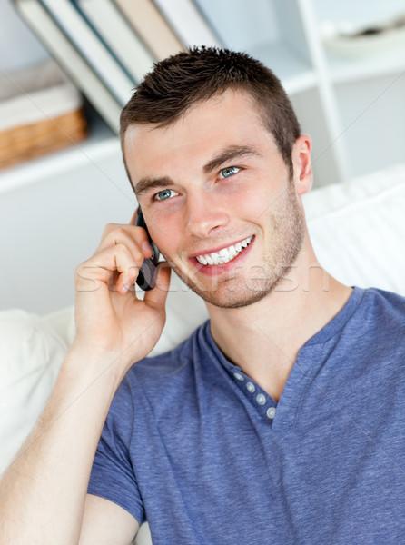 Charyzmatyczny młody człowiek mówić telefonu posiedzenia sofa Zdjęcia stock © wavebreak_media