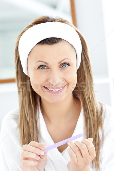 Bright young woman filing her nails smiling at the camera Stock photo © wavebreak_media