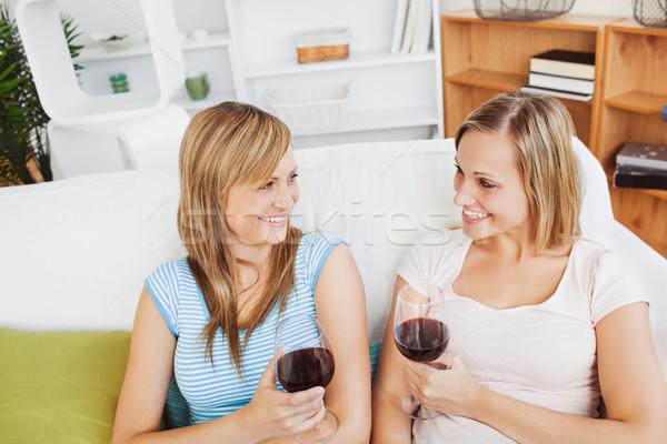 Heureux deux femmes potable vin séance canapé Photo stock © wavebreak_media