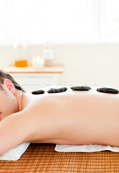 Stock photo: Close-up of a caucasian man with hot stone on his back in a spa center