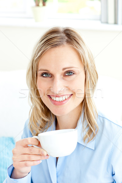 Captivating businesswoman holding a cup sitting on a sofa at home Stock photo © wavebreak_media