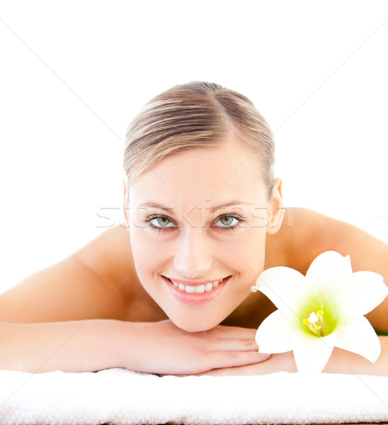 Close-up of a positive woman lying on a massage table with a flower in a health spa Stock photo © wavebreak_media
