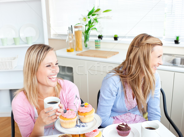 Two laughing female friends eating pastries and drinking coffee in the kitchen at home Stock photo © wavebreak_media