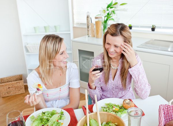 Two women in the kitchen chatting and eating salad with glasses of red wine Stock photo © wavebreak_media