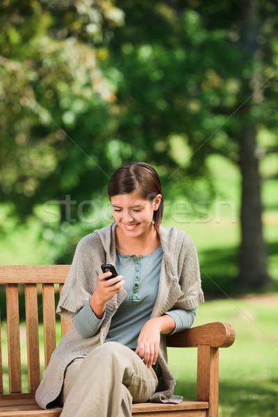Woman phoning on the bench Stock photo © wavebreak_media