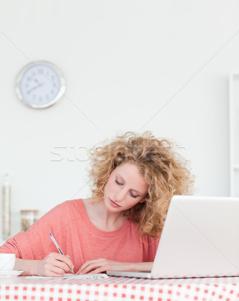 Attractive blonde woman writing while working with her laptop in the kitchen in her appartment Stock photo © wavebreak_media