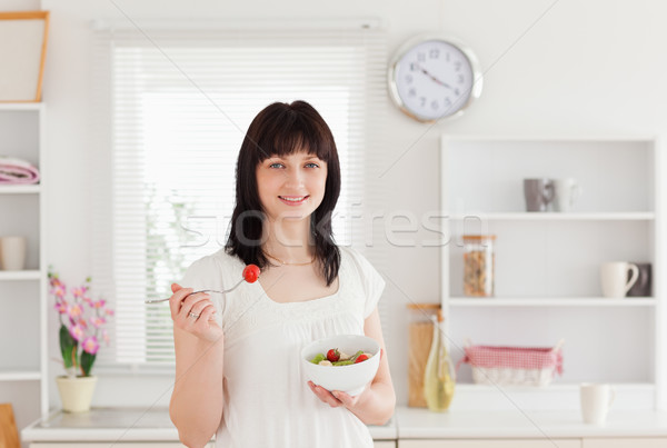 Good looking brunette female eating a cherry tomato while holding a bowl of vegetables in the kitche Stock photo © wavebreak_media