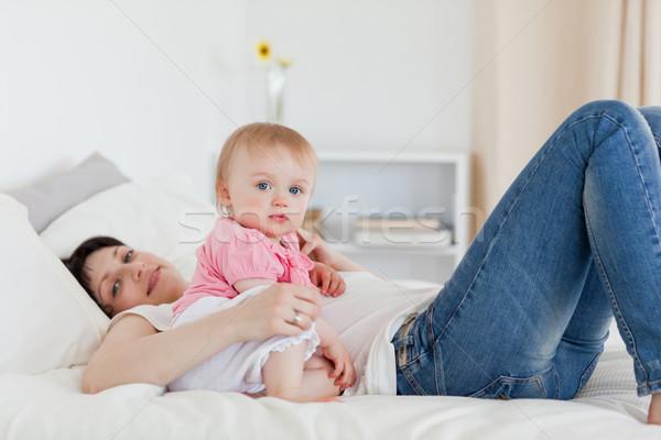очаровательный брюнетка женщину позируют ребенка кровать Сток-фото © wavebreak_media