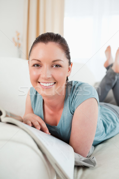 Cute woman reading a magazine while lying on a sofa in the living room Stock photo © wavebreak_media