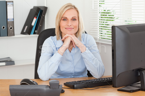 Smiling woman with chin on her hands behind a desk in an office Stock photo © wavebreak_media