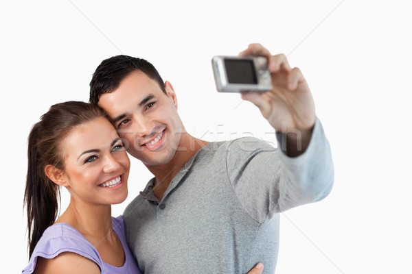 Young couple taking a picture of themselves against a white background Stock photo © wavebreak_media