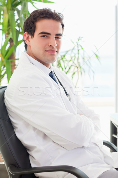 Vue de côté jeunes médecin séance bras pliées Photo stock © wavebreak_media