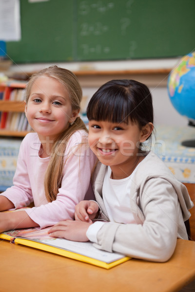 Stock photo: Portrait of smiling schoolgirls reading a fairy tale in a classroom