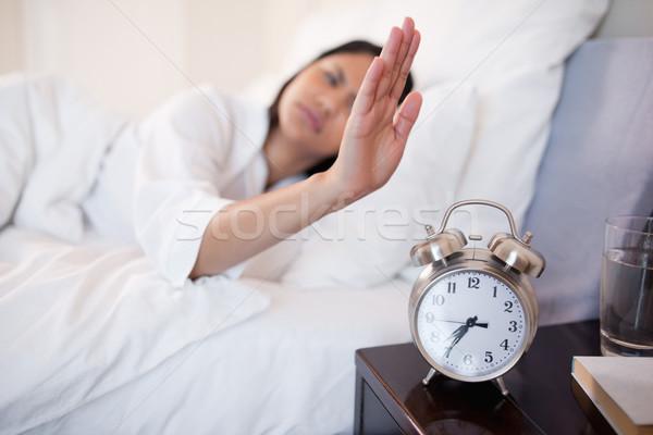 ébresztőóra el fiatal nő ágy hálószoba párna Stock fotó © wavebreak_media